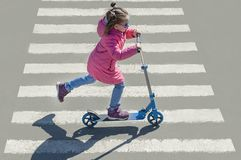 Child riding scooter. Kid on colorful kick board. Active outdoor fun for kids. Sports for preschool children. Little happy girl stock images