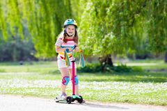 Child riding kick scooter in summer park. Child riding scooter. Kid on colorful kick board. Active outdoor fun for kids. Summer sports for preschool children royalty free stock photos