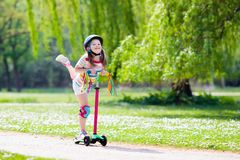 Child riding kick scooter in summer park. Child riding scooter. Kid on colorful kick board. Active outdoor fun for kids. Summer sports for preschool children stock photo