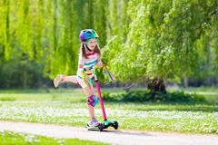 Child riding kick scooter in summer park. Child riding scooter. Kid on colorful kick board. Active outdoor fun for kids. Summer sports for preschool children Royalty Free Stock Photography