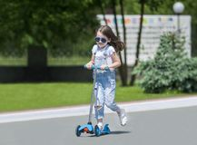 Child riding scooter. Kid on colorful kick board. Active outdoor fun for kids. Summer sports for preschool children. Little happy girl in spring park. The royalty free stock image
