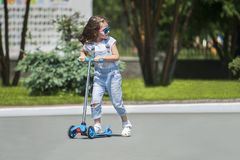 Child riding scooter. Kid on colorful kick board. Active outdoor fun for kids. Summer sports for preschool children. Little happy girl in spring park. The royalty free stock photo