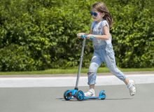 Child riding scooter. Kid on colorful kick board. Active outdoor fun for kids. Summer sports for preschool children. Little happy. Girl in spring park. The royalty free stock photo