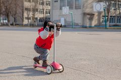 Child riding scooter outdoors, active sport kids.  stock image