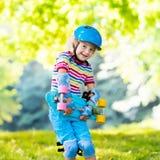 Child riding skateboard in summer park Stock Photos