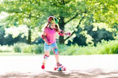 Child riding skateboard in summer park Stock Photography