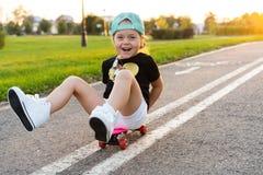 Child riding skateboard in summer park. Little girl learning to ride skate board. Active outdoor sport for school and. Kindergarten kids. Children skateboarding royalty free stock image