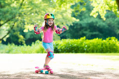 Child riding skateboard in summer park Stock Photo
