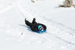 Child riding a sled bundled in warm clothing. Child riding a sled bundled in warm winter clothing royalty free stock photos