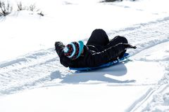 Child riding a sled bundled in warm clothing. Child riding a sled bundled in warm winter clothing stock photos