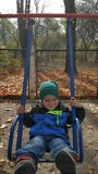 A child is riding on a swing in the fall afternoon. Children`s swing. Vertical video stock footage