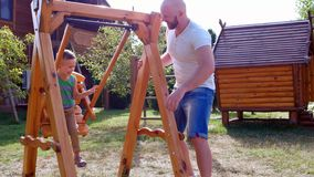 Child riding on a swing, father unrolls swing where his son sits, a boy having fun playing with dad laughing, family on stock video