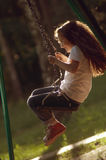 Child riding on a swing royalty free stock photo