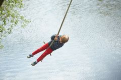 The child is riding on a swing over the water in summer. stock image