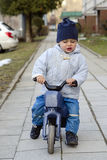 Child riding a toy bike Royalty Free Stock Images