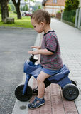 Child riding toy bike Stock Image