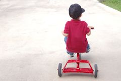 Child riding a tricycle Stock Photo