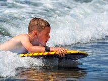 Child riding waves royalty free stock photo