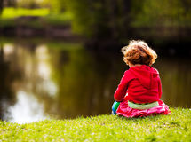 Child on the riverside. Five year old girl sitting on the riverside on a summer day Royalty Free Stock Photo