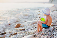 Child on a rock on the beach royalty free stock photos