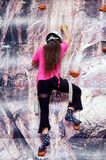 Child rock climbing. Child in pink top climbing a rock wall Royalty Free Stock Photo