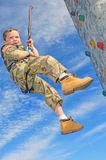 Child on rock climbing wall. Young child rappelling on rock climbing wall Royalty Free Stock Photos