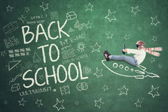 Child with rocket and doodles on the chalkboard Stock Photography