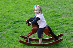 Child on rocking-horse. A beautiful blond caucasian girl child with blue eyes and happy expression in the pretty face riding on her brown wooden rocking-horse in Royalty Free Stock Photography