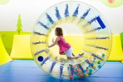 Child play in roller wheel. Kids on trampoline. Child in roller wheel jumping on colorful playground trampoline. Kids jump in inflatable bounce castle on royalty free stock photography