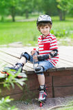 The child on rollers with a bottle of water Stock Photos