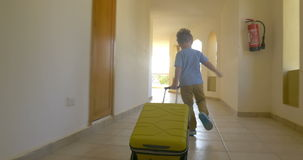 Child with rolling bag running along the hotel stock footage