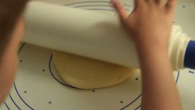 Child rolling the dough. Close-up shot of little kid rolling the dough. Child helps to make tasty home food stock video footage