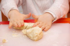 Child rolls the dough Royalty Free Stock Image