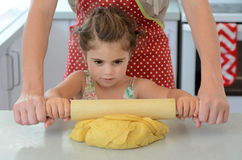 Child rolls dough Royalty Free Stock Photos