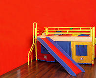 Child room. Colorful bed in childs room with red wall Stock Photography