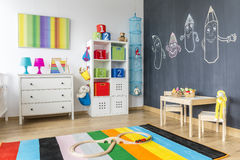 Child room with colorful rug. View of child room with colorful rug and blackboard wall Royalty Free Stock Images