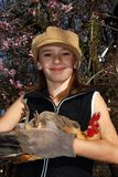 Child with rooster. Little girl with hat and garden gloves holding a rooster with almond blossoms Royalty Free Stock Images
