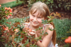 Child with rose flower in spring garden Royalty Free Stock Images