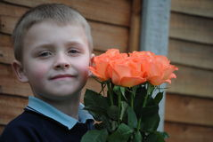 Child with roses. Little, blonde boy with roses for his Mum royalty free stock photo