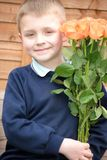 Child with roses. Little, blonde boy with roses for his Mum royalty free stock photos