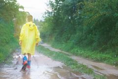 Child in rubber boots playing royalty free stock image