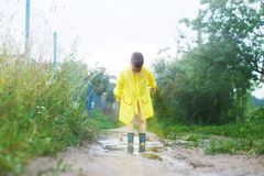 Child in rubber boots playing royalty free stock photography