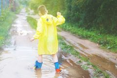 Child in rubber boots playing stock image