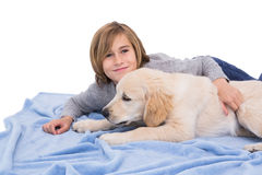 Child rubbing his dog lying on a blanket Stock Photo
