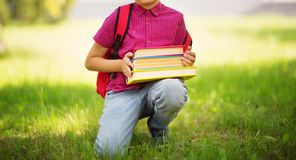Child with rucksack sitting in the park near school royalty free stock photography