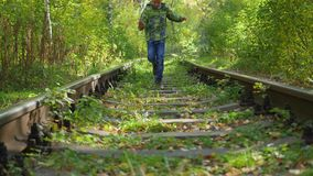 The child run by rail. The child goes by rail the Park stock video footage