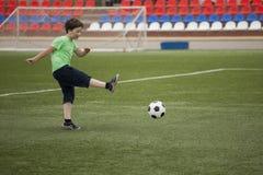Child run soccer football player. Boy with ball on green grass.  Stock Photo