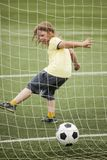 Child run soccer football player. Boy with ball on green grass.  Stock Image