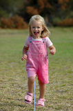Child running. A blond active little pretty toddler girl in pink clothes with happy laughing expression in her beautiful face running in the park outdoors Stock Image