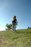 Child Running. A little girl runs up a grassy hill towards a blue sky. The back of a child as she runs away Stock Images